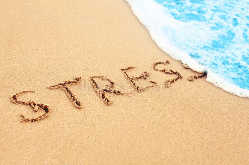 Stress free travel. The wave on sea beach washes away sign stress on sand royalty free stock photo