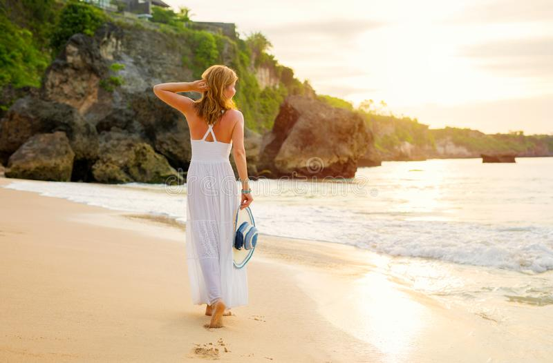 Stress free woman in white summer dress walking on the beach at sunset stock image