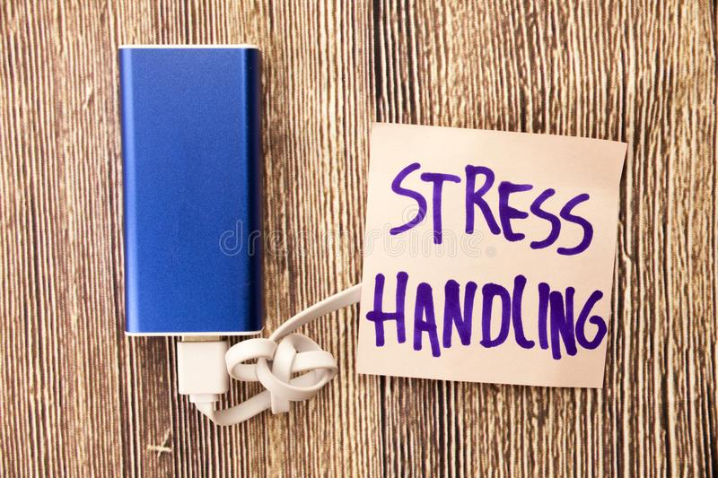 Stress Handling is presented on a note paper in black color. Energy storage device of blue color with cable on wooden background. stock images