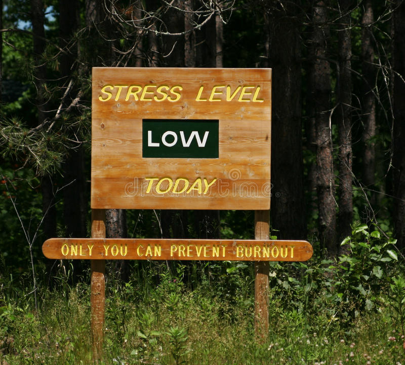 Stress Level low sign. Wooden sign in the forest stating stress level low today, only you can prevent burnout stock image