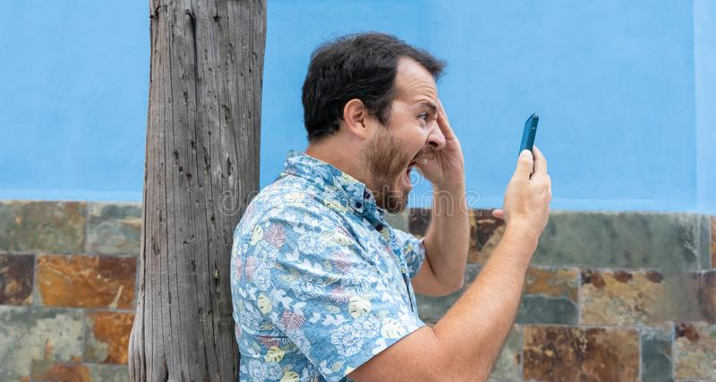 Stress and mad person, yelling and shouting to the phone in a call with blue background. Crazy Angry man calling with aggressive. And pressure is arguing royalty free stock images
