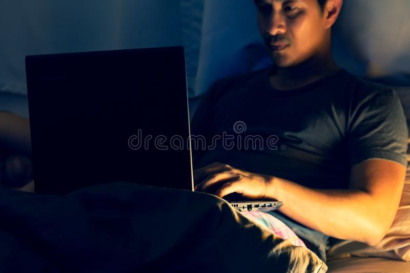 Stress man lying in bed and working with laptop late at night at home. stock image