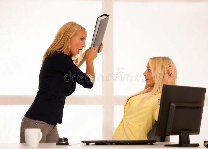 Stress mobbing - Angry worker wonts to hit a boss with a folder royalty free stock photography