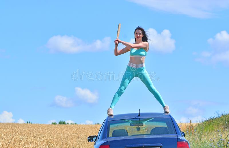 Stress, nerves and psychos concept. Girl with the bat is on the roof of the car.  royalty free stock photos