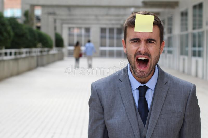 Stress out businessman with a note on his forehead stock images
