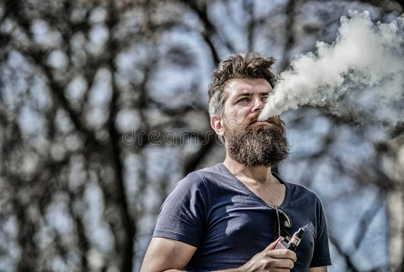 Stress relief concept. Bearded man smoking vape. Smoking electronic cigarette. Man long beard relaxed with smoking habit. Man with beard and mustache breathe stock photography