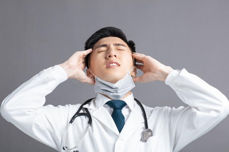 Stress and tired young Doctor Wear Medical Mask.  stock photography