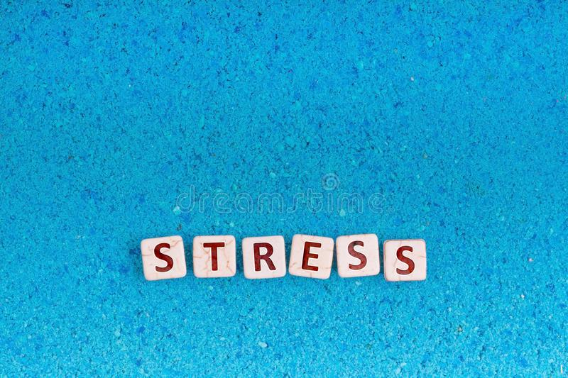 Stress word on stone. Stress word write in square white stone on blue sand, free space for your text stock photo