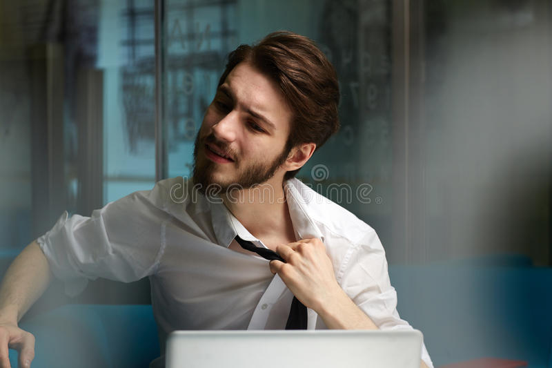 Stress at work. Tired man relieving his tie during late work in office stock images