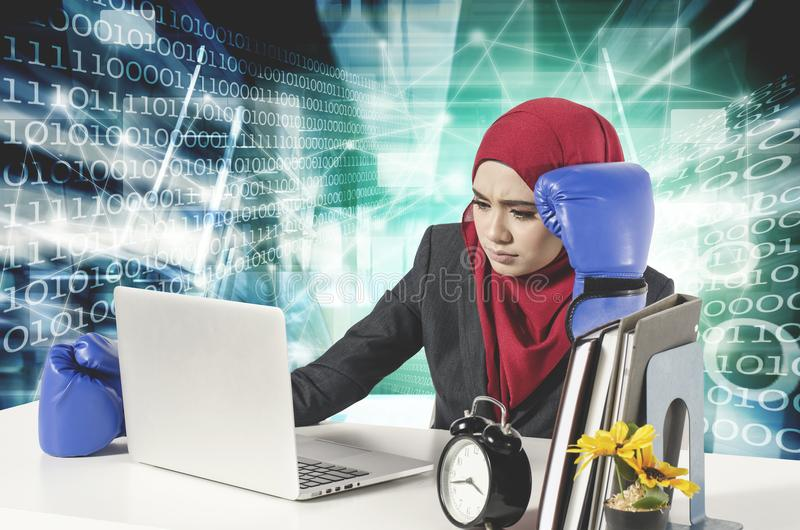 Stress young businesswomen with boxing glove look at her laptop. Cyber security business concept with abstract double exposure stock photography
