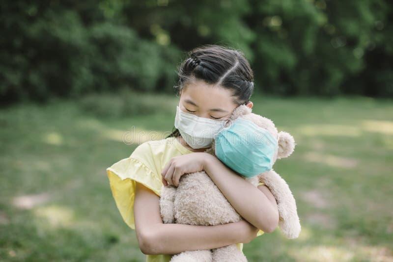 Stressa en liten flicka som håller i leksaksbjörn med en skyddsmask royaltyfria bilder
