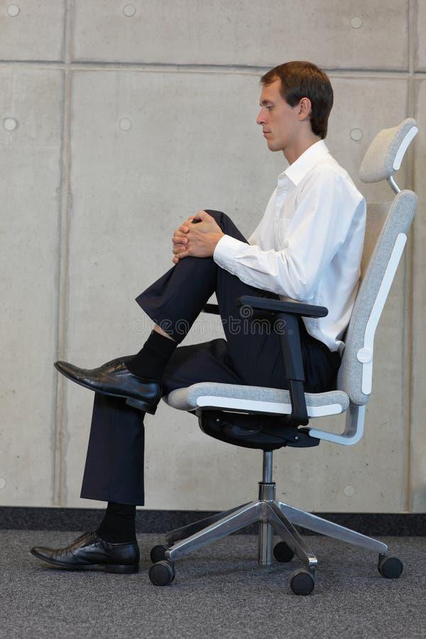 Stressabbau in der Büroarbeit - bemannen Sie das Trainieren auf Stuhl stockfotografie