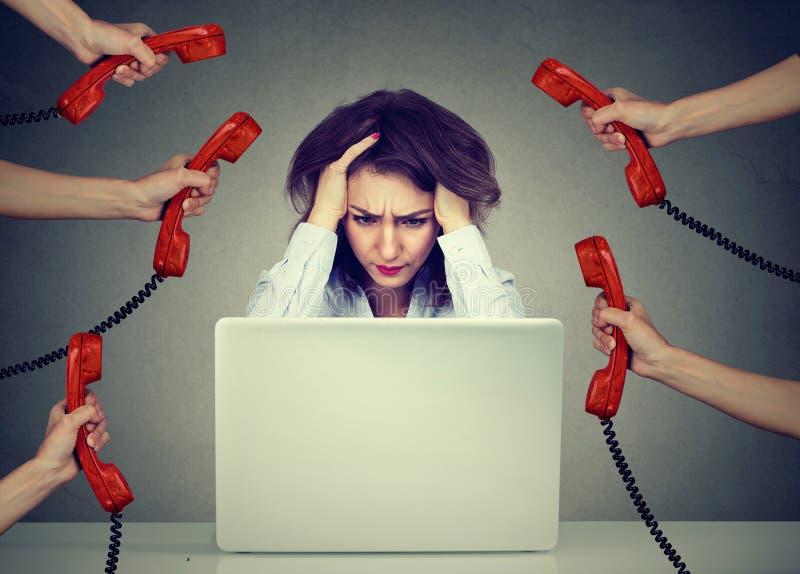 Stressad affärskvinna som arbetar på en bärbar dator som förkrossas av för många påringningar arkivbild