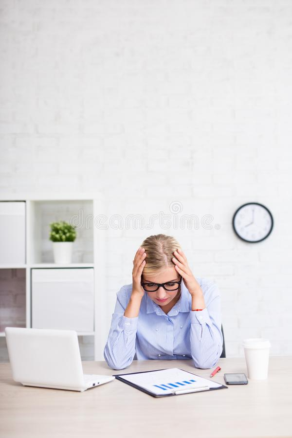 Stressad affärskvinna som i regeringsställning sitter med kopieringsutrymme över w arkivbild