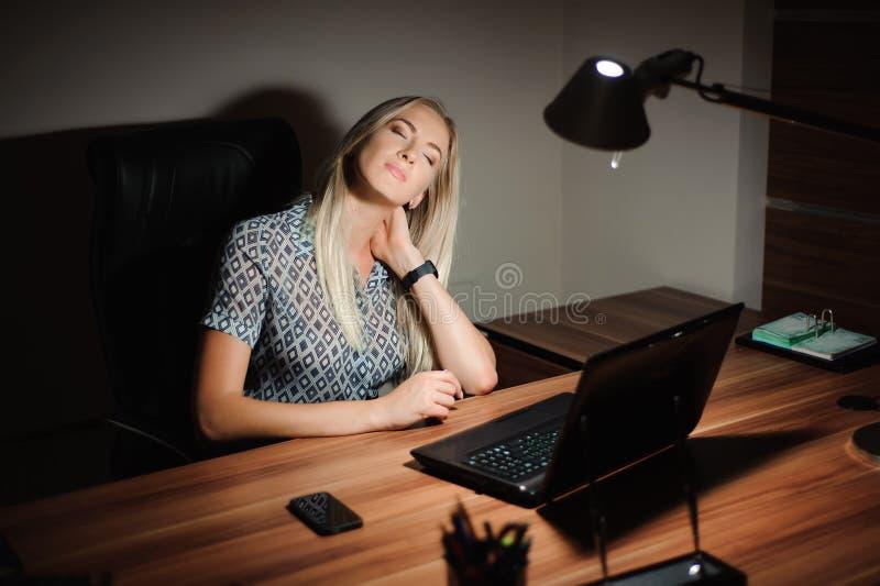 Stressad affärskvinna som sitter på kontorsskrivbordet och tänker lösningen, medan arbeta sent framme av en dator royaltyfri bild