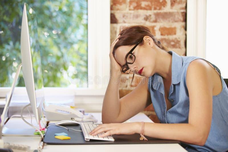 Stressad affärskvinna Working At Computer i modernt kontor arkivbild