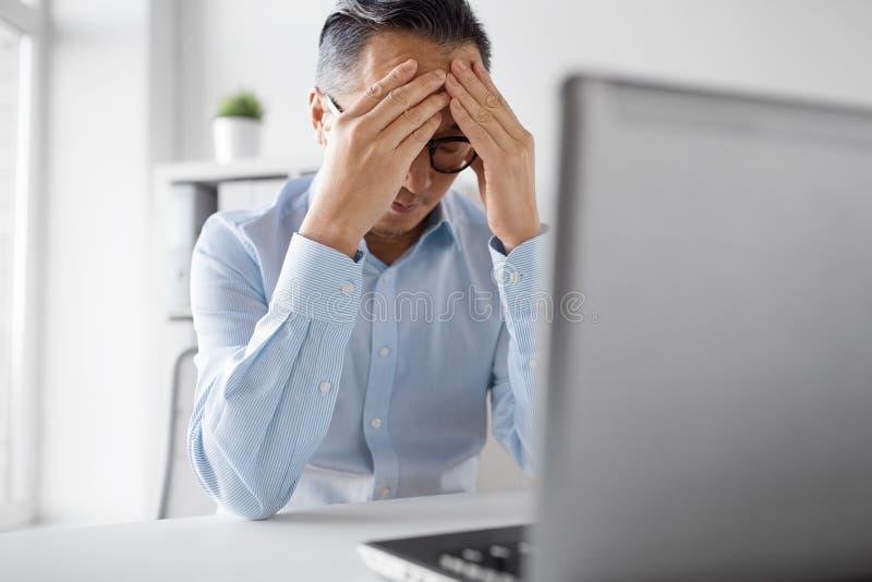 Stressad affärsman med bärbar datorarbete på kontoret royaltyfri bild