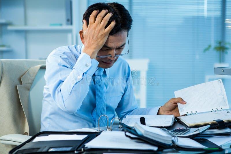Stressad affärsman med ett stort belopp av arbete arkivbilder