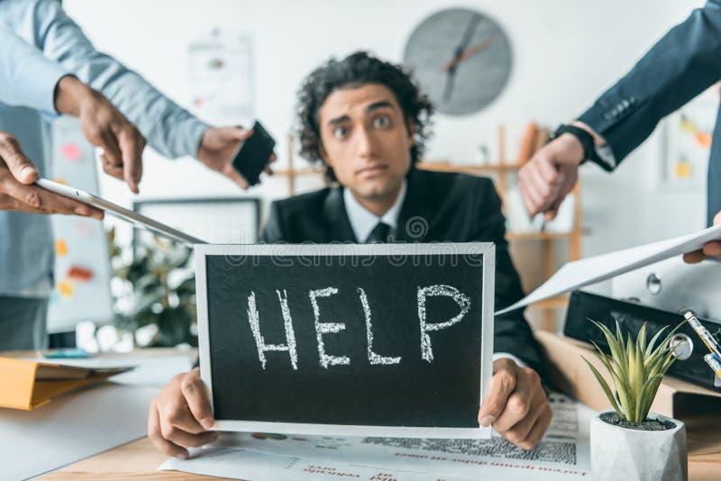 stressad affärsman med hjälpsvart tavla som har problem med stopptid med att stå för kollegor fotografering för bildbyråer