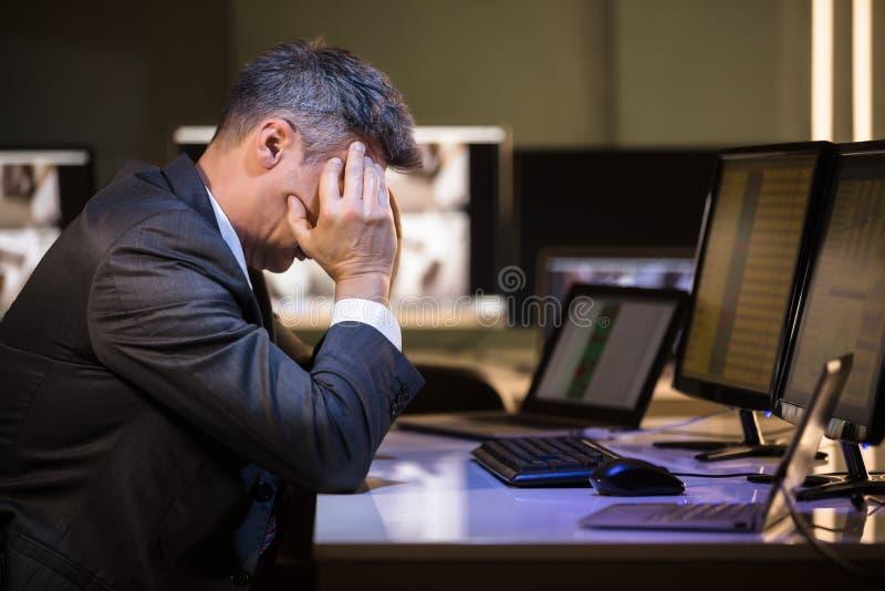 Stressad affärsman som i regeringsställning sitter royaltyfri foto