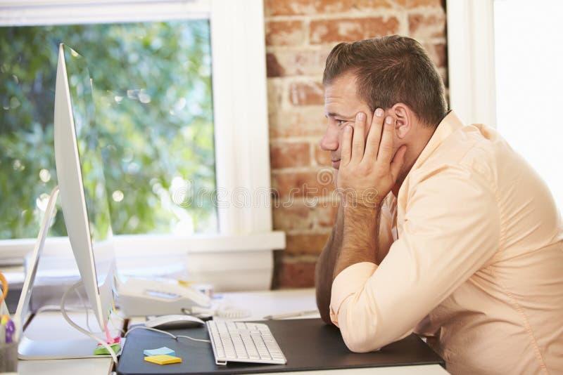 Stressad affärsman Working At Computer i modernt kontor royaltyfri bild
