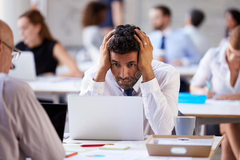 Stressad affärsman Working On Laptop i upptaget kontor royaltyfri bild