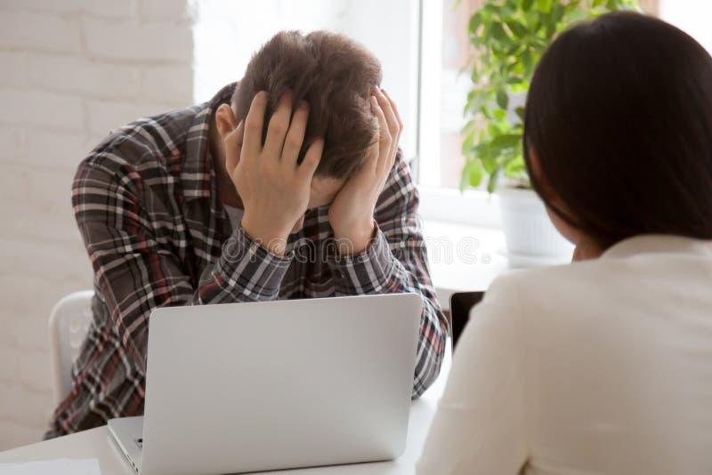 Stressad anställd som ner känner sig med företagsaffärskollaps royaltyfri foto