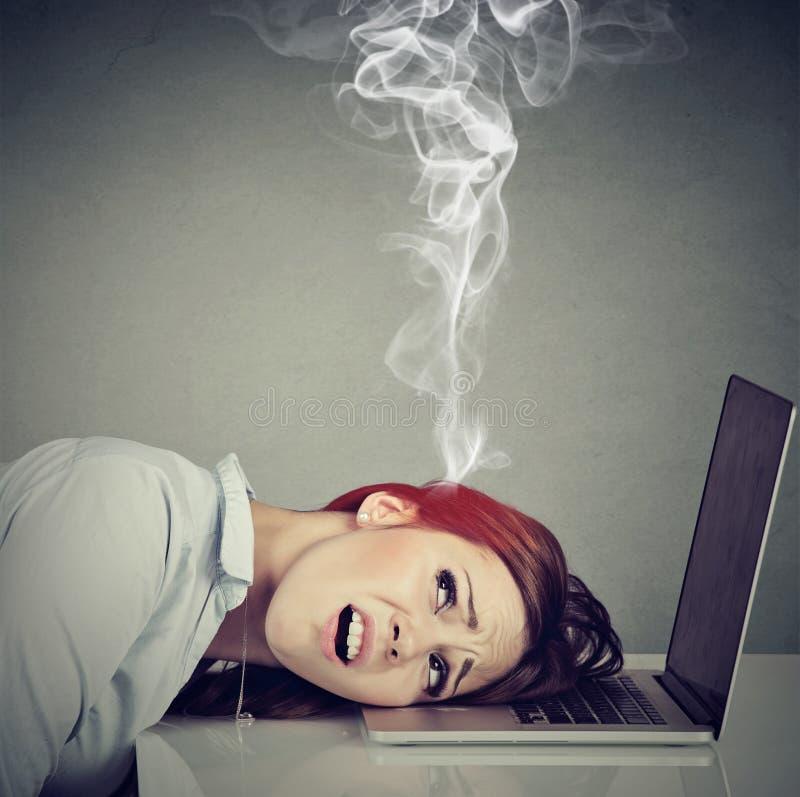 Stressad anställdkvinna med den överhettade hjärnan genom att använda bärbara datorn royaltyfria bilder