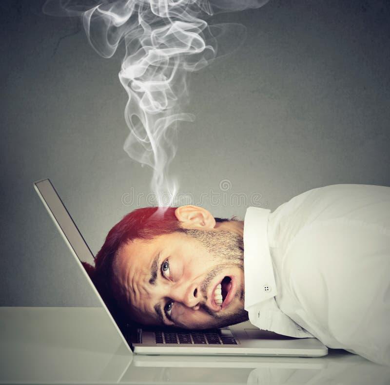 Stressad anställdman med den överhettade hjärnan genom att använda bärbara datorn arkivfoton