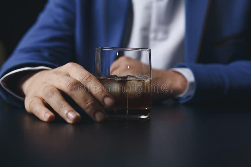 Stressad asiatisk affärsman som rymmer ett exponeringsglas av whisky honom sova och datadiagram, affärsdokument på kontorsskrivbo arkivfoto