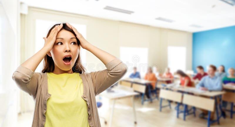 Stressad asiatisk kvinna som rymmer till hennes huvud på skola arkivfoto