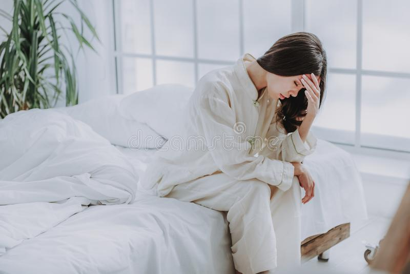 Stressad asiatisk kvinna som uttrycker besvikelse i sovrum fotografering för bildbyråer