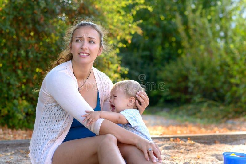 Stressad barnmoder som tröstar hennes skriande son fotografering för bildbyråer