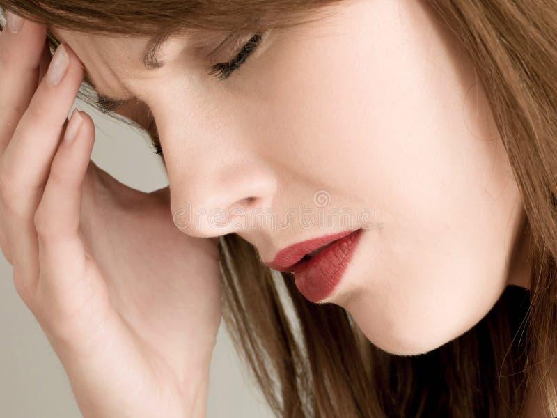Stressad deprimerad ung kvinna som rymmer hennes huvud arkivfoto