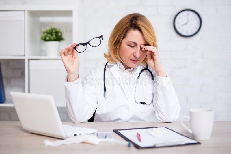 Stressad eller trött mogen kvinnlig doktor som arbetar i modernt kontor royaltyfri bild