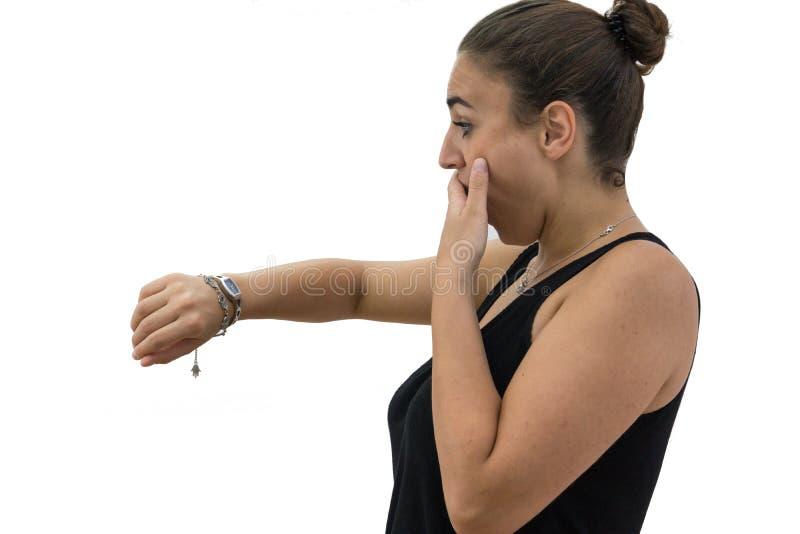 Stressad flicka som ser klockan på vit bakgrund royaltyfria bilder