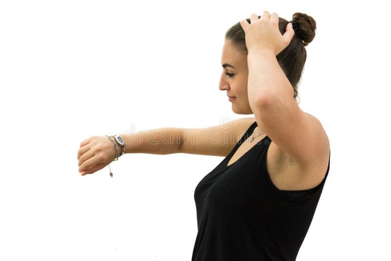 Stressad flicka som ser klockan på vit bakgrund royaltyfria foton