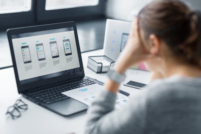 Stressad formgivare med användargränssnittet på bärbara datorn arkivfoton