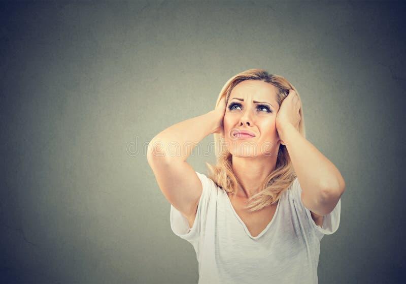 Stressad frustrerad ung kvinna som täcker henne öron med händer arkivbilder
