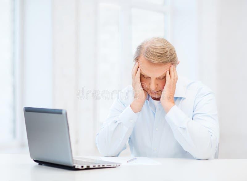 Stressad gamal man som hemma fyller en form fotografering för bildbyråer