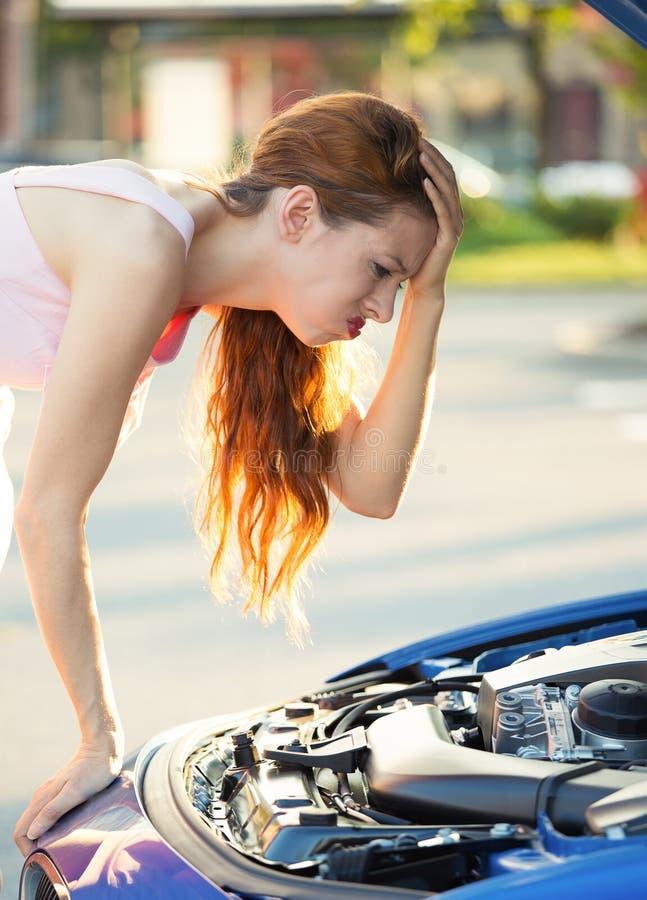 Stressad ilsken ung kvinna framme av hennes brutna ner bil royaltyfria bilder