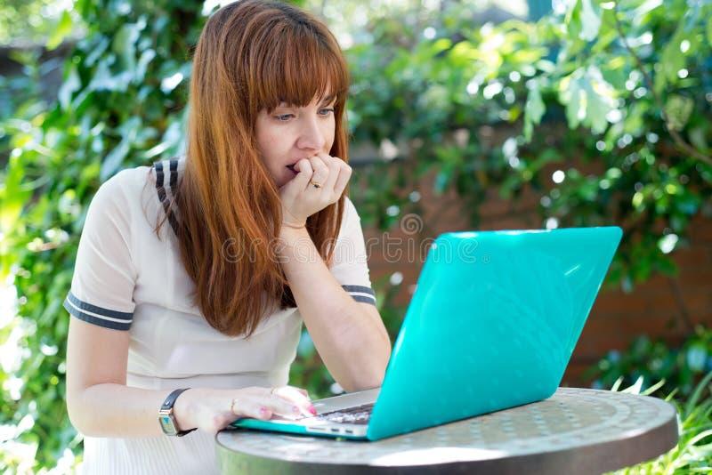Stressad kvinna med datoren i trädgården arkivfoto