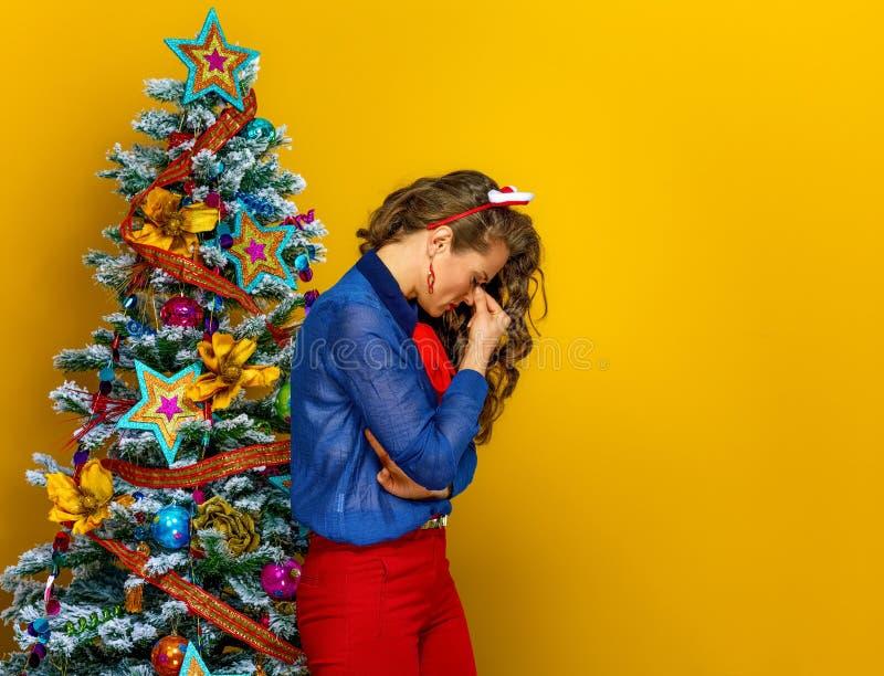 Stressad kvinna nära julgranen som isoleras på guling royaltyfri foto