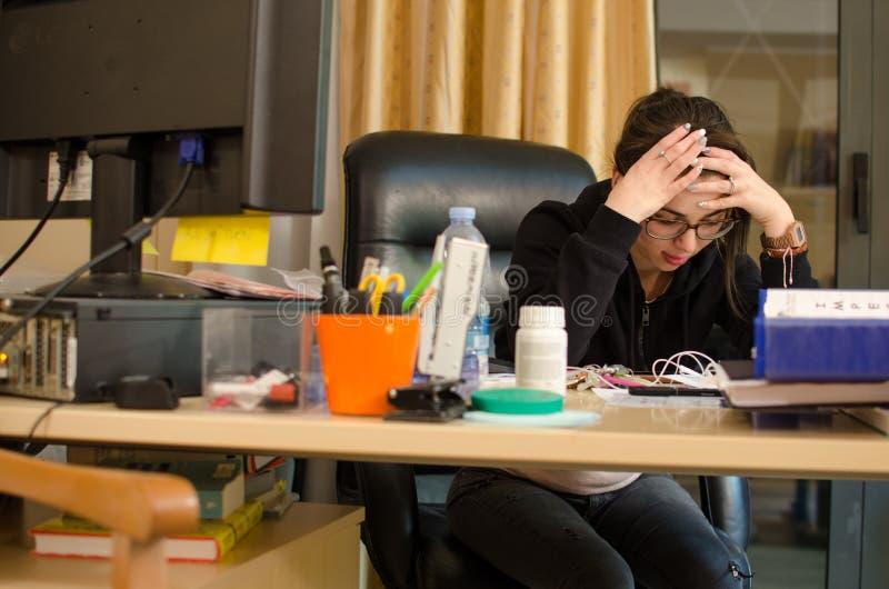 Stressad kvinna på arbete med datoren som är främst av henne fotografering för bildbyråer