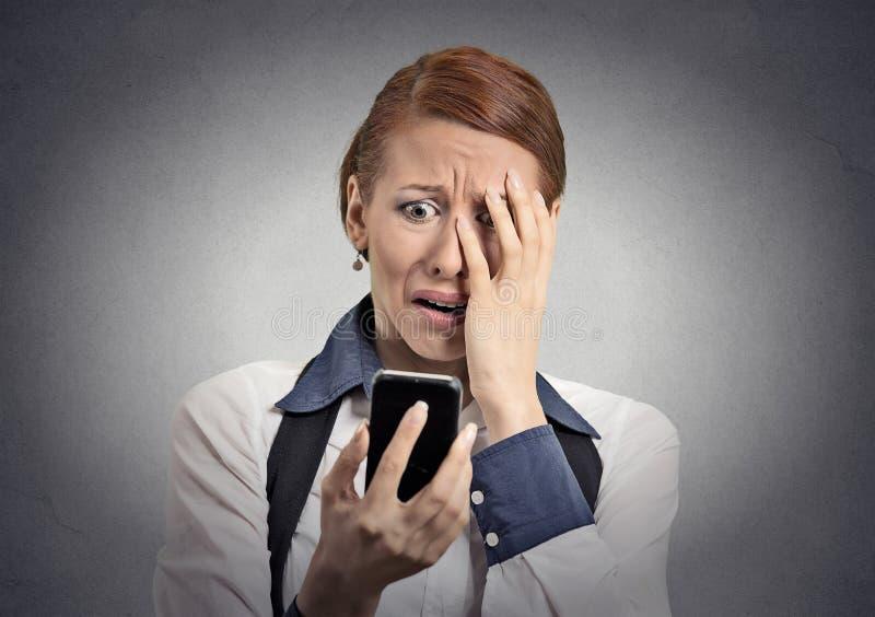 Stressad kvinna som är chockad med meddelandet på smartphonen royaltyfri foto