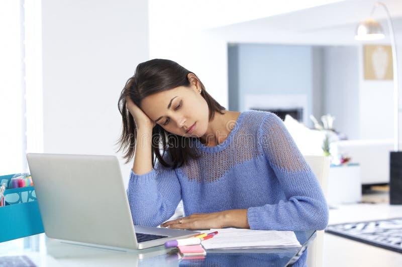Stressad kvinna som arbetar på bärbara datorn i inrikesdepartementet arkivfoto
