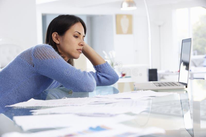 Stressad kvinna som arbetar på bärbara datorn i inrikesdepartementet royaltyfria bilder