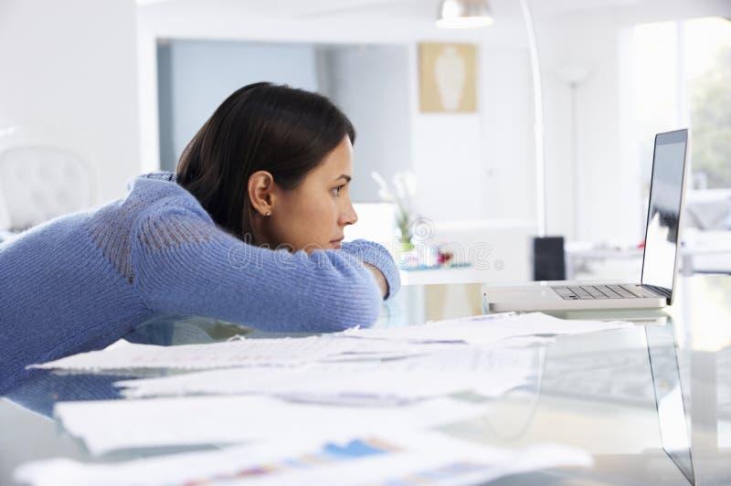 Stressad kvinna som arbetar på bärbara datorn i inrikesdepartementet royaltyfri fotografi