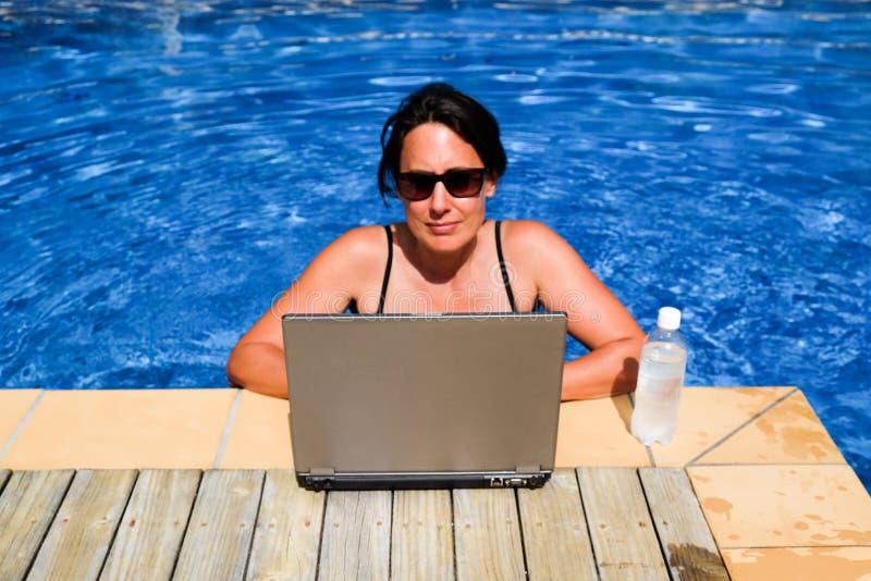 Stressad kvinnlig utövande arbetsnarkoman som arbetar på bärbar datordatoren royaltyfri bild