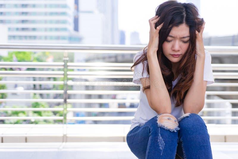 Stressad ledsen kvinna med huvudvärk Uppriven kvinna som rymmer hennes huvud I fotografering för bildbyråer